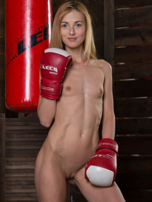 Thin blonde girl with A-cup tits poses nude other than a pair of boxing gloves