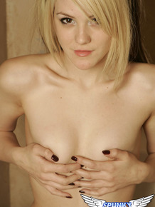 Natural blonde girl covers up her private parts while posing in the nud