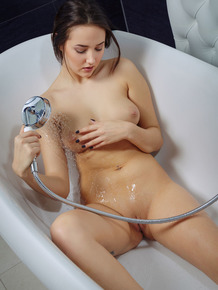 Teen beauty Patricia B wets her yummy pussy while naked in a bathtub
