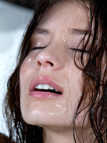 Brunette girl Irina J gets wet as she sinks into a bathtub filled with water