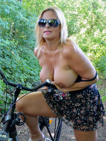 Busty plump mature Chrissy bicycling topless with her huge big boobs swaying