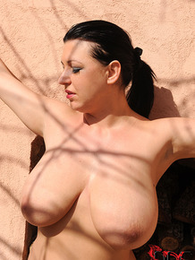 Busty female is left tired to a wall in just her black stockings