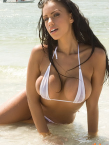 Beach bunny teases and taunts in a wet string bikini in the water