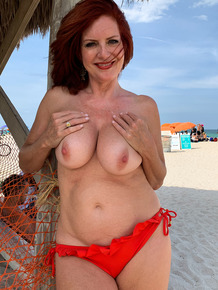 Redhead amateur removes her bikini to go naked at a public beach