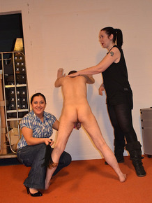 Clothed females whip and spank a naked man's ass after he worships their boots