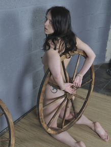 Naked brunette is affixed to a wagon wheel with ropes on her knees