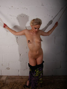 Short haired blonde endures nipple torture while restrained in dungeon setting