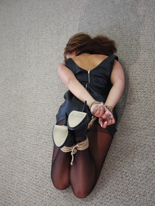 Clothed female is left hogtied and gagged on carpeted floor of empty room