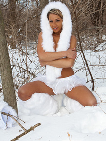 Nikki Sims poses in the woods during the winter in white tutu and boots