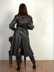 Brunette female dons long leather coat in leather boots and stockings