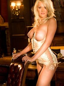 Foxy blonde centerfold Caitlin Ferguson sports huge fake tits in posh office