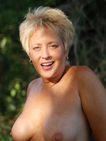 Older blonde Tracy Lick slips off USA themed lingerie to nude in Florida swamp