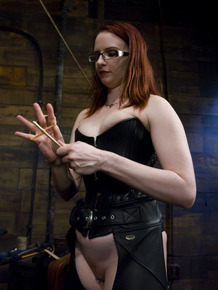 Red-haired dominatrix in leather uniform punished guy's most sensitive parts