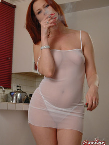 Fair skinned redhead Mina goes topless while smoking in the kitchen