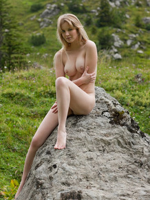 Naked blonde Belinda posing on rocks with her hot ass feeling the mountain air