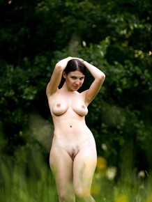 Big titted Laura relaxes naked outdoors and poses on her knees in the grass