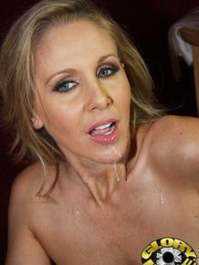 Mature MILF Julia Ann sucks off a large cock via a gloryhole in wall