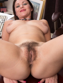 Boss lady Gina Louise undresses behind her desk to display her hairy snatch