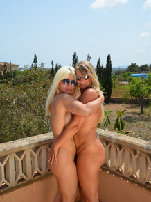 Older blonds share girl on girl kiss before slipping out of dresses on balcony