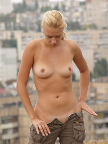 Blonde model Angie T climbs a hill in the city before stripping naked