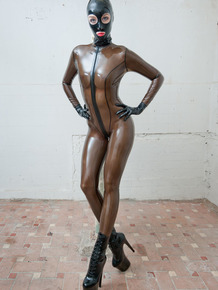 Tall slender model in brown latex bodysuit & mask posing in stiletto heels