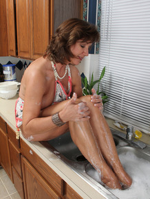 Mature MILF soaks her feet in kitchen sink while petting her snatch