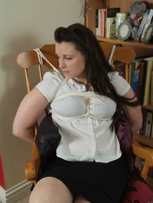 Brunette woman struggles against rope bindings in a rocking chair