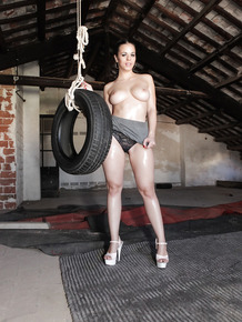Brunette with big ass Nacho Vidal oiled up & swinging on a tire in garage