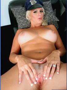 Sexy blond MILF in lady cop uniform denudes her stunning assets