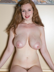 Natural redhead Misha Lowe uncovers her big natural and bush as she disrobes