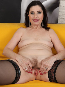Mature lady with black hair Barbarella dildos her trimmed muff after disrobing