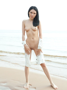 Dark haired female Lily J getting naked on dessereted nudist beach