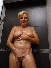 Aged housewife with short hair and a few extra kilos masturbates in the shower