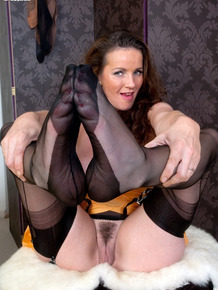 Solo model with a tramp stamp peels off vintage lingerie in seamed stockings
