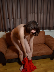 Brunette female unzips her full bodysuit to show her bald pussy in the nude