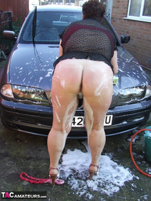 Fat old lady Kinky Carol bares her big tits while soaping up during a car wash
