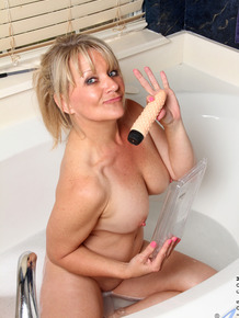 Mature lady pleasures her pussy in the bathtub with her sex toy collection