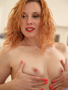 Sexy redhead MILF Monita toying her naked pussy with dildo in front of mirror
