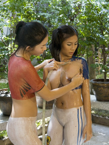 Young Asian lesbians wash off body paint with garden hose in courtyard