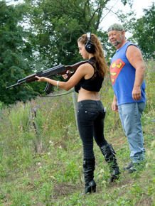 Latina teenager Gigi Rivera goes topless while firing off a rifle in woods