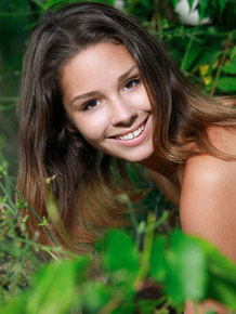 Petite teen Arina F removes black bra and panty set in front of undergrowth